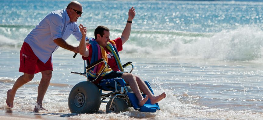 Carer pushing a beach wheelchair with a young man enjoying the beach