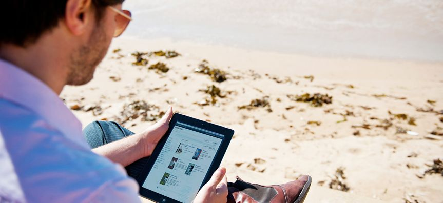 Man paying rates online at beach