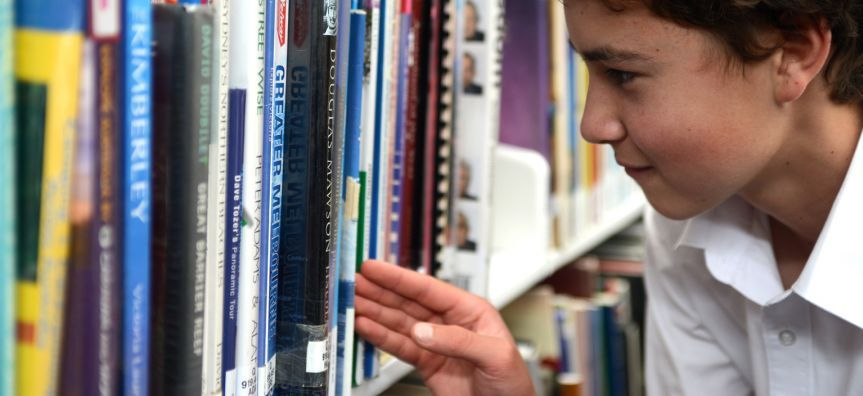 Boy looking for books to read in library