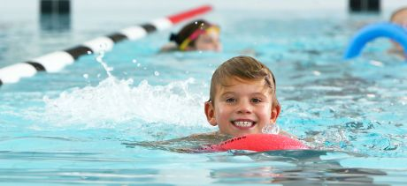 Young boy swimming with kickboard