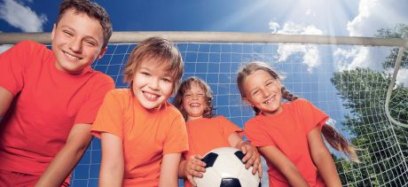 Children with soccer ball in front of goalposts